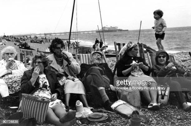 A group of elderly people relax in deckchairs on the beach at Brighton Photographer Tony RayJones created most of his images of the British at work...