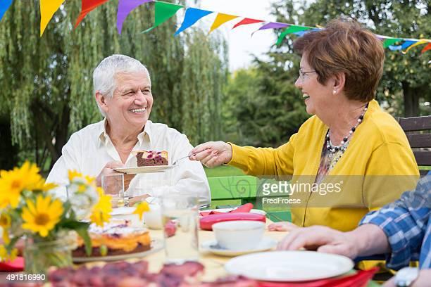 Gruppe der älteren Menschen Sitzen im Garten-Tisch