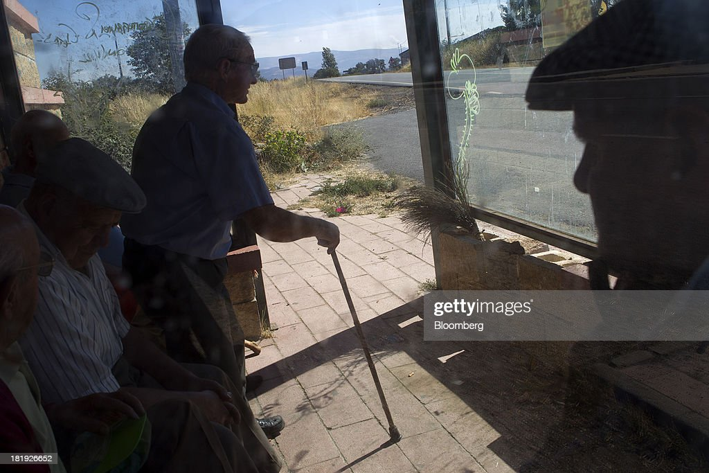 A group of elderly Spanish men sit in the shade of a bus shelter and talk in Becedas, Spain, on Thursday, Sept. 26, 2013. Prime Minister Mariano Rajoy is increasingly dependent on the pension reserve fund as it reaps lower returns on Spanish sovereign debt, which comprise 97.5 percent of its investments. Photographer: Antonio Heredia/Bloomberg via Getty Images