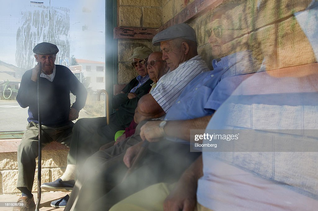 A group of elderly Spanish men sit on a covered bench and talk in Becedas, Spain, on Thursday, Sept. 26, 2013. Prime Minister Mariano Rajoy is increasingly dependent on the pension reserve fund as it reaps lower returns on Spanish sovereign debt, which comprise 97.5 percent of its investments. Photographer: Antonio Heredia/Bloomberg via Getty Images