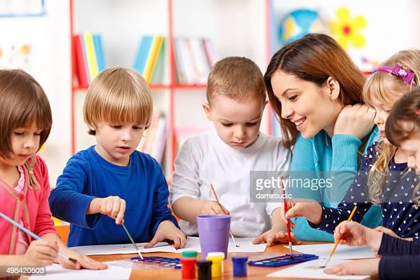 Groupe d'âge élémentaire des enfants avec professeur à la classe d'Art