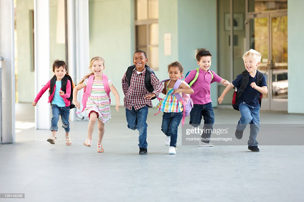 Group Of Elementary Age Schoolchildren Running Outside : Stock Photo