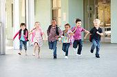 Grupo de escolares de edad primaria corriendo afuera