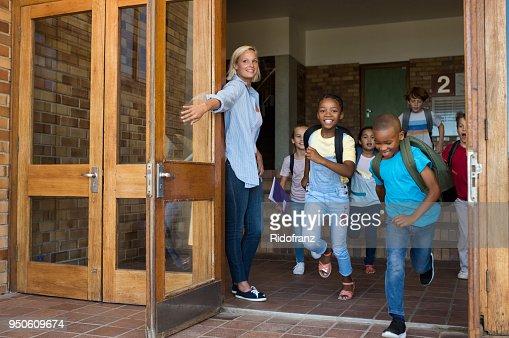 Group of elementary children running outside school : Stock Photo