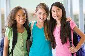 Group of female elementary school friends standing in corridor