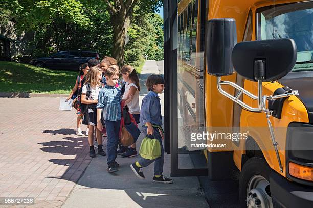 Group of elementary school kids getting in yellow school bus.