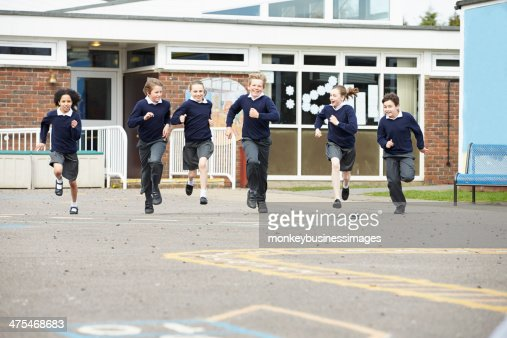 Group Of Elementary School Pupils Running In Playground : Stock Photo