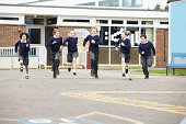 Group Of Elementary School Pupils Running In Playground Running Towards Camera