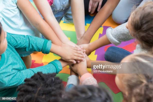 Group of elementary students with hands together