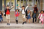 A group of energetic elementary school kids leaving school