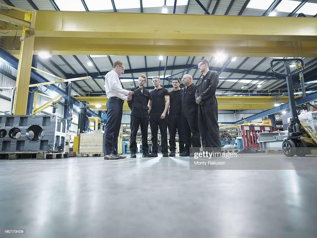 Group of engineers and apprentices in engineering factory