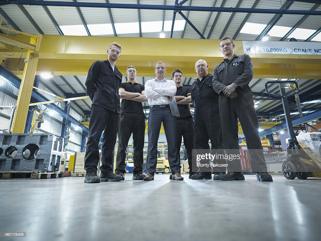 Group of engineers and apprentices in engineering factory, portrait