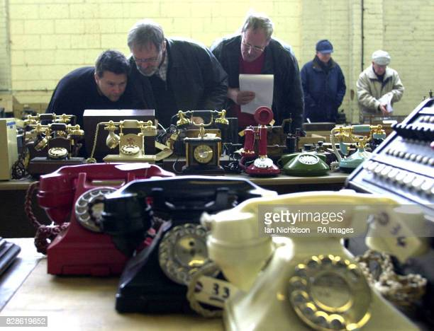 A group of enthusiasts examine telephone handsets pictured which form part of a lot available in auction of memorabilia Saturday 22nd February 2003...