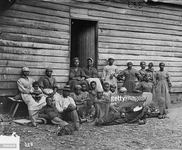 A group of escaped slaves outside a cabin Escaped slaves were known as contrabands after the Union General Benjamin Butler announced that any slaves...