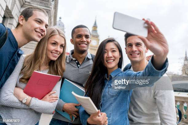 Group of exchange students in London taking a selfie outdoors
