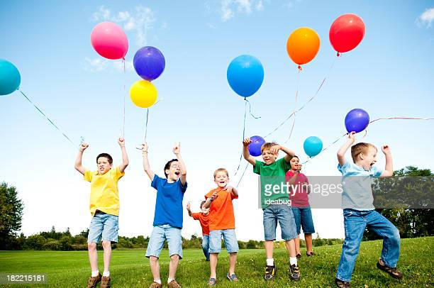 Group of Excited Boys Jumping and Celebrating Outside