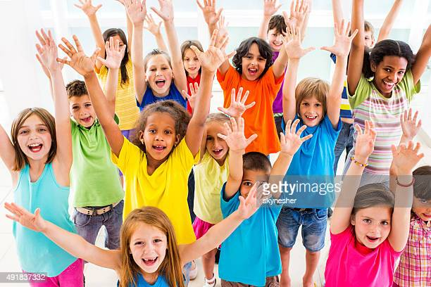 Group of excited children with raised arms looking at camera.