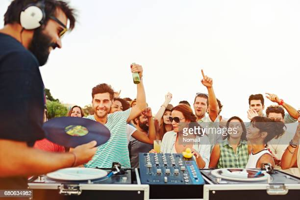 Group of excited friends dancing by DJ at beach
