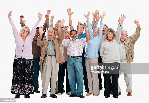 A group of excited people raising their arms in the air
