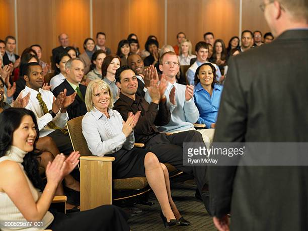 Group of executives applauding for man leading seminar in auditorium