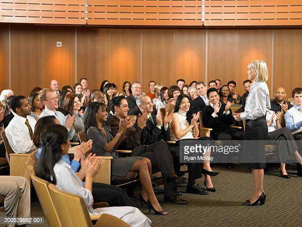 Group of executives applauding for woman leading seminar in auditorium