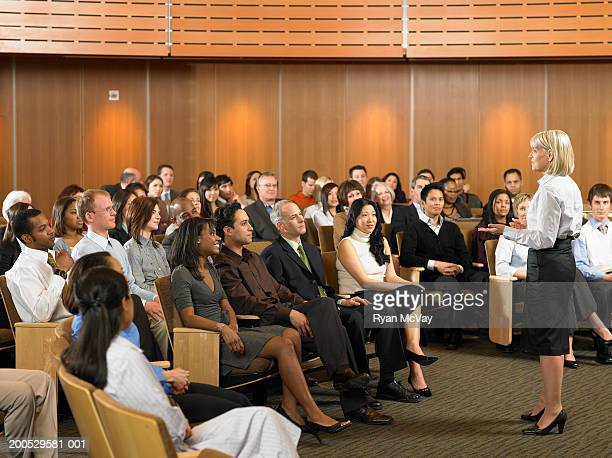 Group of executives listening to woman leading seminar in auditorium