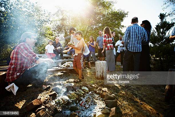 Group of family and friends roasting oysters