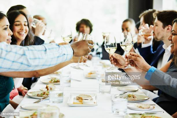 Group of family and friends toasting during celebration meal in restaurant