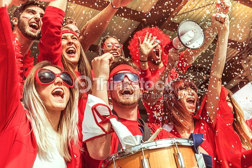 group of fans dressed in red color watching a sports event : Stock Photo