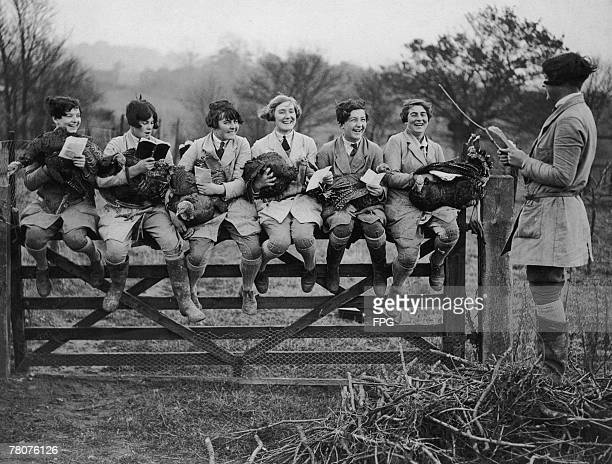 A group of farm workers holding turkeys as they practice singing Christmas carols on a poultry farm in Welwyn Hertfordshire 29th November 1929