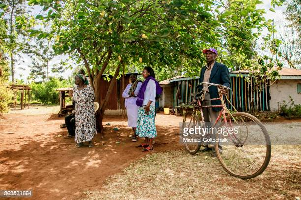 A group of farmers at a farm on which plants grow with the support of the irrigation system of local farming cooperative Mitooini The field of a farm...