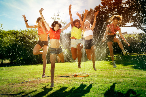 Group of femal teenagers jumping through a sprinkl