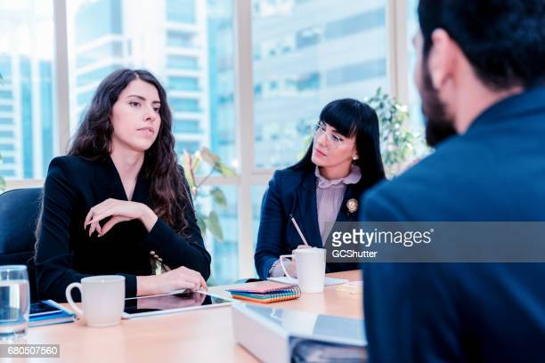 Group of female business executives taking interview of a man