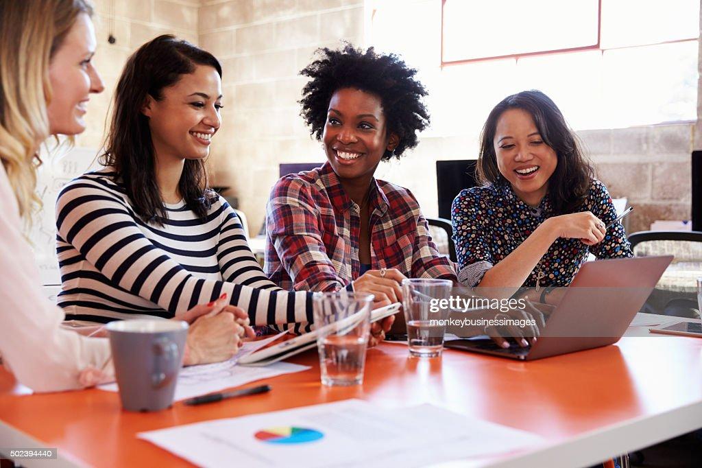 Groupe de femmes designers ayant une réunion au bureau moderne