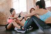 Group of female exercising in gym. Three young woman doing physical workout in gym.