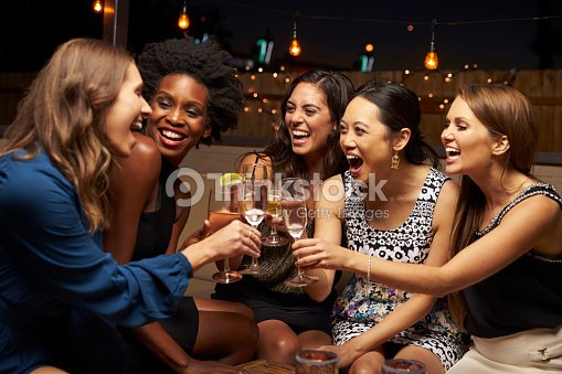 Group Of Female Friends Enjoying Night Out At Rooftop Bar : Stock Photo
