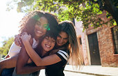 Three happy young women embracing each other on city street and smiling. Group of friends enjoying outdoors on city street.