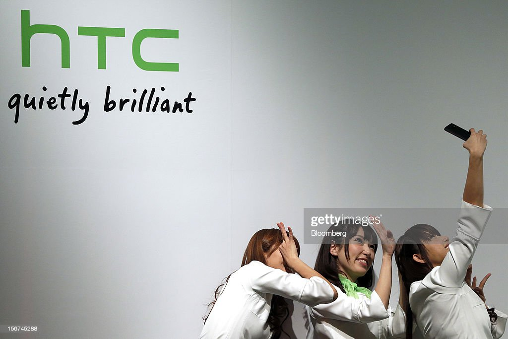 A group of female models pose for a photograph using the HTC J Butterfly smartphone, produced by HTC.Corp., during the unveiling event in Tokyo, Japan, on Tuesday, Nov. 20, 2012. Taiwan's HTC Corp. needs to improve its global brand awareness to gain share in China, and its newly unveiled model is likely to help the vendor do that. Photographer: Kiyoshi Ota/Bloomberg via Getty Images