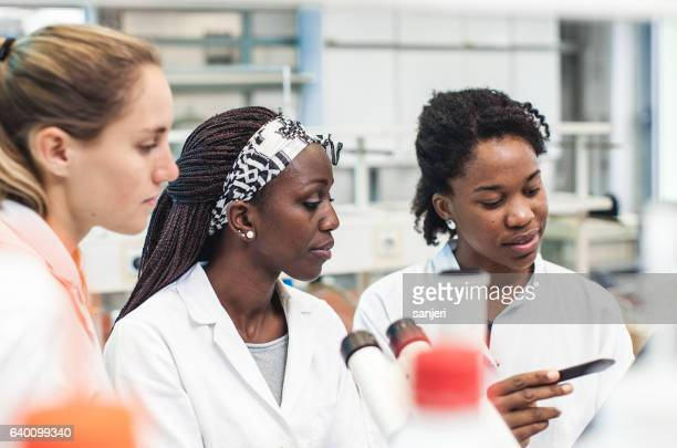 Group of Female Scientists Discussing in a Laboratory