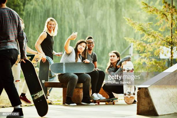 Group of female skateboarders taking selfie with smartphone after skating in skate park on summer morning