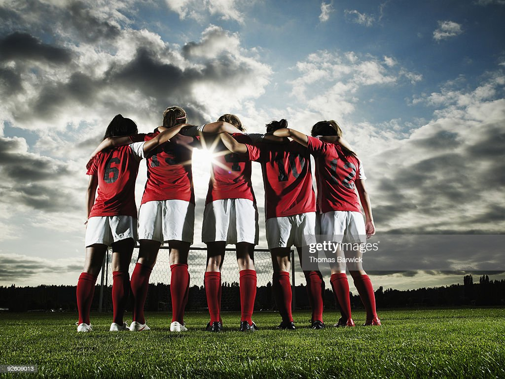 Group of female soccer players embracing : Stock Photo