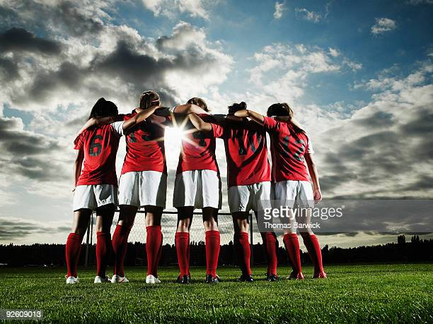 Group of female soccer players embracing
