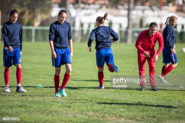 Group of female soccer players warming up with their coach on a playing field.