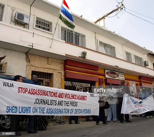 A group of fifty people hold a banner during a protest in front of Gambia's high commission 22 December 2004 in Dakar The group demonstrated in the...