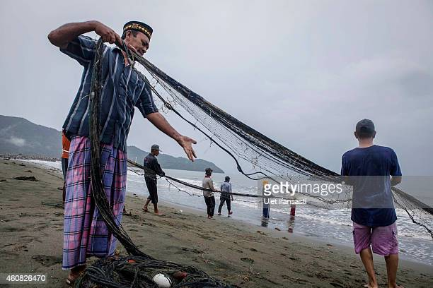 A group of fishermen pull fishing nets on the coastline in Lamtutui village on December 25 2014 in Banda Aceh Indonesia Aceh was the worst hit...