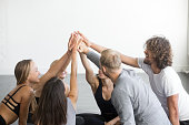 Group of fit happy people giving high five in fitness studio room, celebrating success. Setting goals, achieving team result. Teamwork, unity, support, motivation, active healthy life benefits concept