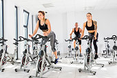 Group of fit people training at exercising class. Cardio workout. Indoor cycling.