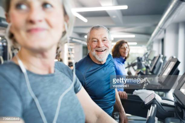 Group of fit seniors on treadmills working out in gym, man smiling