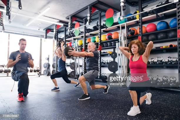 Group of fit seniors with personal trainer in gym exercising with medicine balls