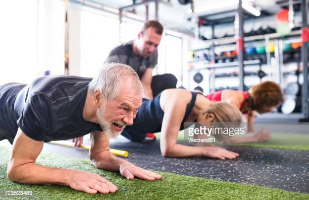 Group of fit seniors with personal trainer in gym